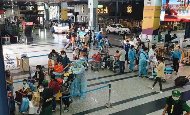 Chùm ảnh: Người dân mặc đồ bảo hộ kín mít trên những chuyến bay trở về Sài Gòn sau kỳ nghỉ Tết Nguyên đán - Ảnh 4.