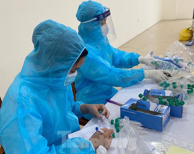 Dân văn phòng Hà Nội xếp hàng lấy mẫu xét nghiệm COVID-19 trong ngày đầu đi làm - Ảnh 2.