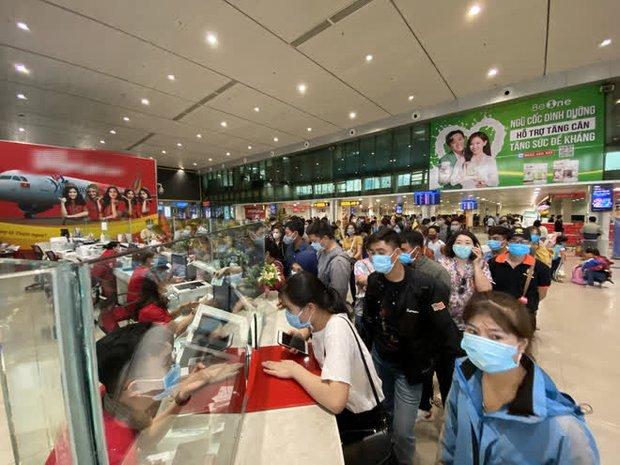 Hành khách xếp hàng dài ở sân bay Tân Sơn Nhất để đổi trả vé Tết vì dịch Covid-19 - Ảnh 1.