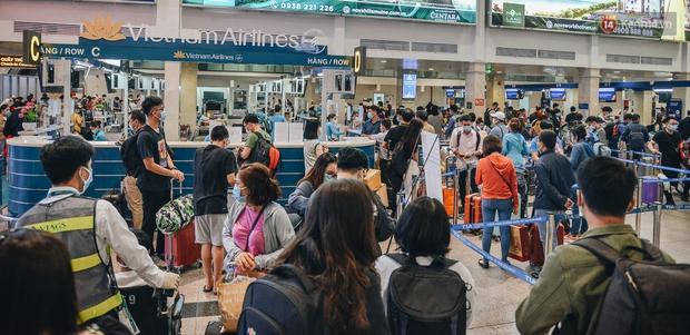 Sân bay Tân Sơn Nhất kích hoạt chế độ chống dịch nghiêm ngặt, hành khách mặc đồ bảo hộ về quê ăn Tết - Ảnh 1.