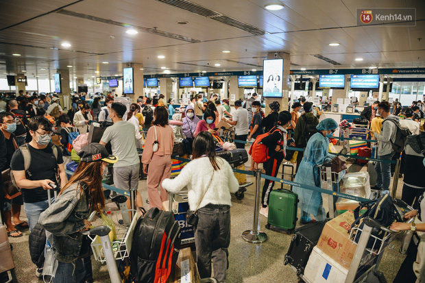 Sân bay Tân Sơn Nhất kích hoạt chế độ chống dịch nghiêm ngặt, hành khách mặc đồ bảo hộ về quê ăn Tết - Ảnh 9.
