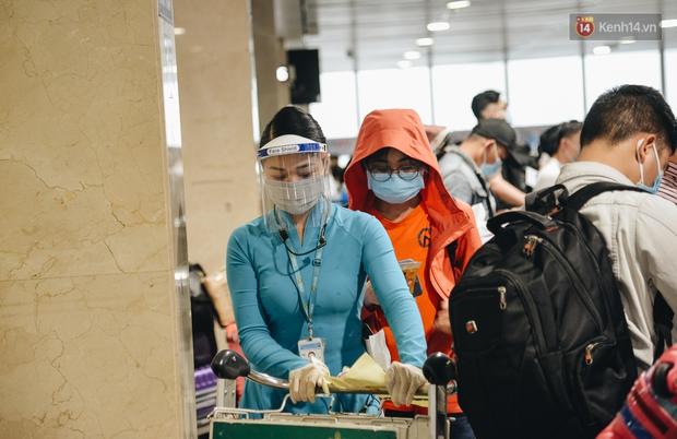 Sân bay Tân Sơn Nhất kích hoạt chế độ chống dịch nghiêm ngặt, hành khách mặc đồ bảo hộ về quê ăn Tết - Ảnh 2.