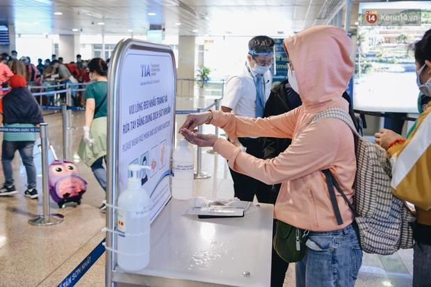 Sân bay Tân Sơn Nhất kích hoạt chế độ chống dịch nghiêm ngặt, hành khách mặc đồ bảo hộ về quê ăn Tết - Ảnh 7.