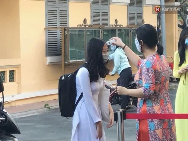 Ngày đầu tiên đi học sau 1 tháng nghỉ Tết: Học sinh chạy vội vì trễ giờ, khẩu trang kín mít vào lớp, dừng các hoạt động dưới sân trường - Ảnh 1.