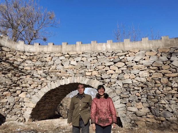 Thấy vợ lội sông bị trượt chân, chồng quyết xây cầu trong 5 năm với hơn 20.000 hòn đá, khoảnh khắc hoàn thành công trình gây xúc động cực mạnh - Ảnh 1.