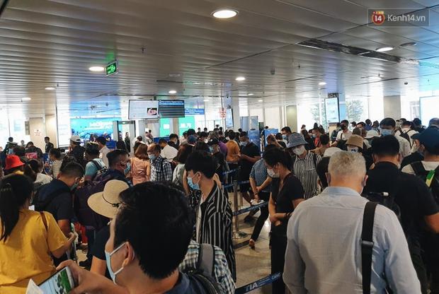 Khu vực kiểm tra an ninh ở Sân bay Tân Sơn Nhất lộn xộn như chợ vỡ, hành khách mỏi mòn đợi chờ - Ảnh 2.
