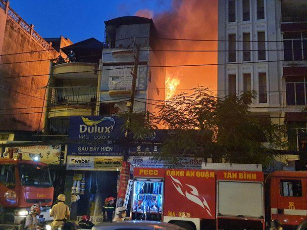 TP.HCM: Cháy dữ dội tại cửa hàng sơn, hàng trăm người đứng dưới đường theo dõi dập lửa - Ảnh 1.