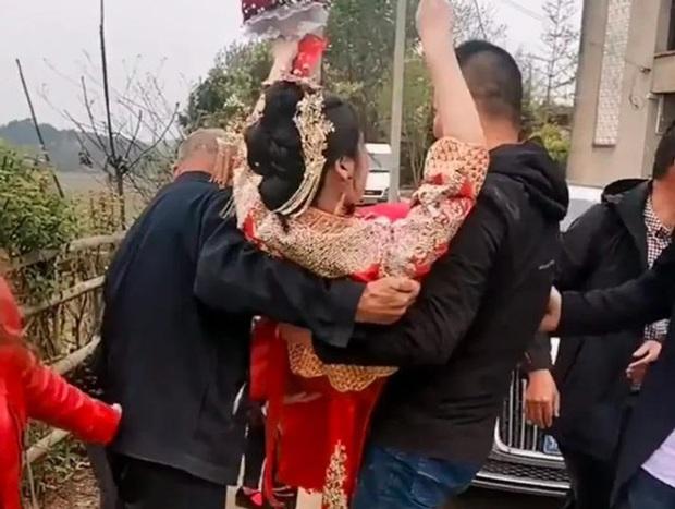 Bố chồng bế con dâu từ xe hoa vào nhà, phản ứng chú rể gây tranh cãi - Ảnh 2.