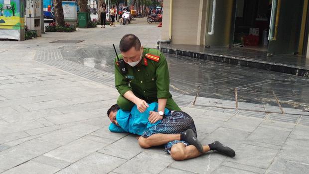 Hà Nội: Khống chế đối tượng có biểu hiện ngáo đá, tấn công người đi đường bằng chất bẩn, gạch đá - Ảnh 1.