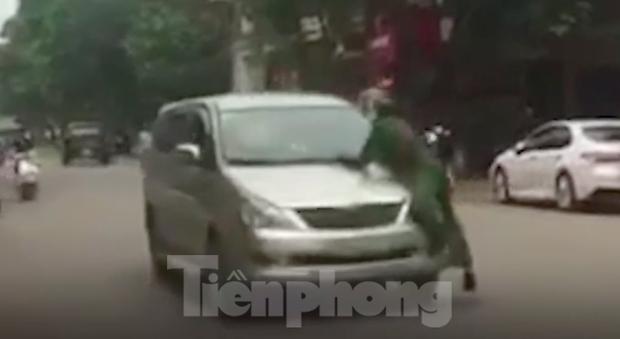 Lao ô tô vào tổ tuần tra rồi bỏ chạy, cảnh sát phải đu bám trên nắp ca pô hàng trăm mét - Ảnh 1.