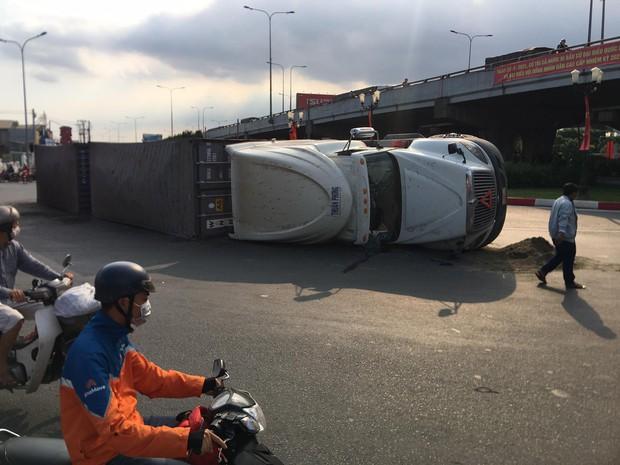 TP.HCM: Xe container lật ngang ngay ngã tư, 2 tuyến Quốc lộ tê liệt hàng giờ - Ảnh 1.