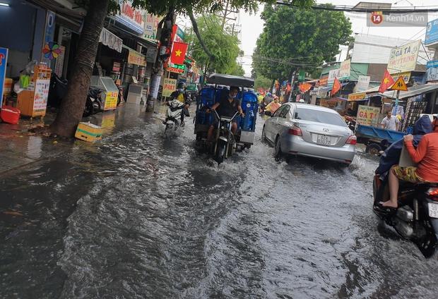Đường Sài Gòn lại thành sông sau mưa, nước chảy cuồn cuộn như thác đổ - Ảnh 7.