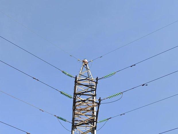 """TP.HCM: Cô gái ngồi trên ngọn cột điện cao thế """"hóng gió"""" suốt 3 tiếng, nhiều người hoảng sợ - Ảnh 1."""