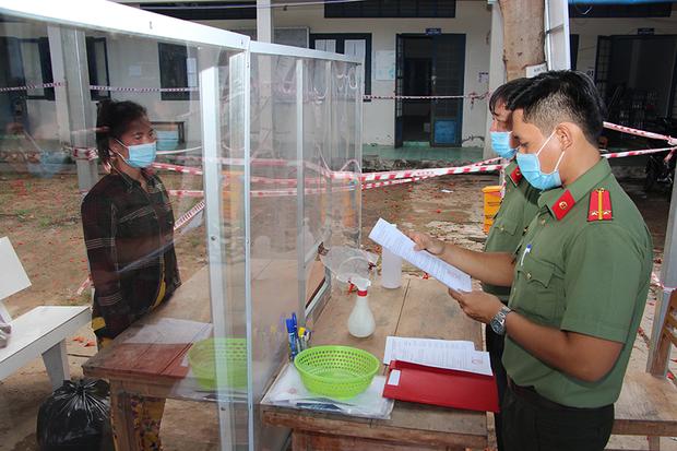 Công an An Giang đọc lệnh bắt giam bị can qua vách chắn phòng dịch - Ảnh 1.