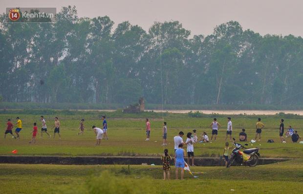 Chùm ảnh: Người Hà Nội kéo nhau ra bãi đất trống đá bóng thả diều, cởi bỏ khẩu trang cho mát bất chấp dịch Covid-19 - Ảnh 2.