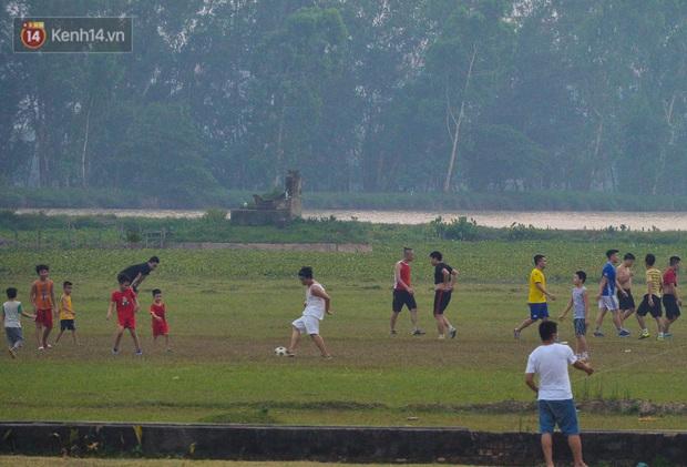 Chùm ảnh: Người Hà Nội kéo nhau ra bãi đất trống đá bóng thả diều, cởi bỏ khẩu trang cho mát bất chấp dịch Covid-19 - Ảnh 3.
