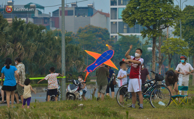 Chùm ảnh: Người Hà Nội kéo nhau ra bãi đất trống đá bóng thả diều, cởi bỏ khẩu trang cho mát bất chấp dịch Covid-19 - Ảnh 1.