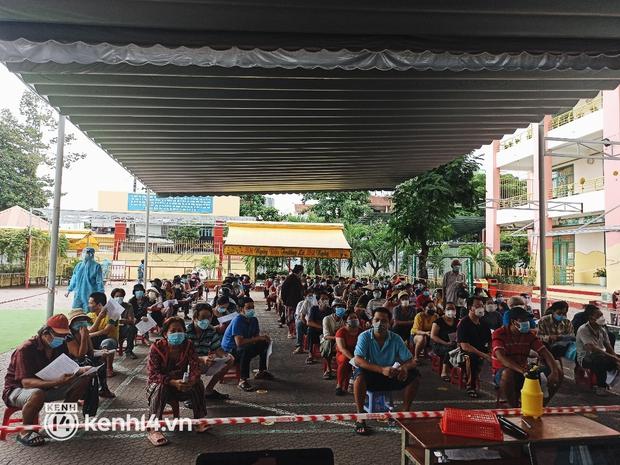 Người dân ở TP.HCM ngồi đợi dưới mưa để tiêm vaccine Vero Cell - Ảnh 2.