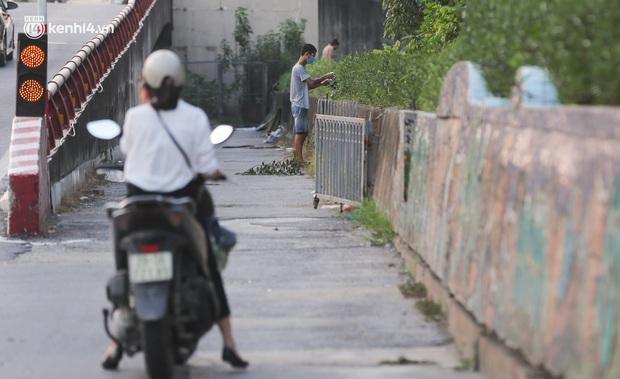 Ảnh: Né hàng rào thép gai, ném đồ qua tường cho người trong khu phong toả, người đàn ông vẫn bị công an phát hiện - Ảnh 11.