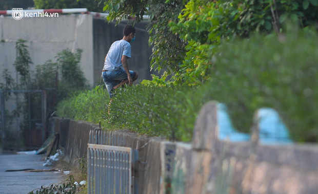 Ảnh: Né hàng rào thép gai, ném đồ qua tường cho người trong khu phong toả, người đàn ông vẫn bị công an phát hiện - Ảnh 13.