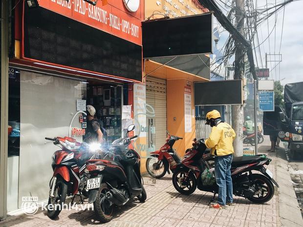 Ngày đầu quận 7 tái hoạt động: Quán ăn bán trực tiếp cho người dân mang về, cửa hàng điện thoại, tiệm sửa xe đã mở lại - Ảnh 7.
