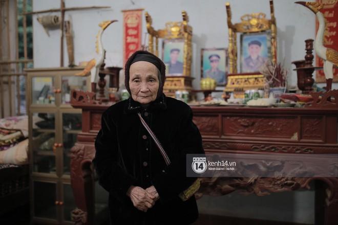 Bà đứng trước bàn thờ tổ tiên, hôm nay bà mặc chiếc áo nhung đẹp nhất - Ảnh: Mai Lân
