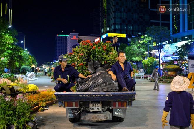 Hai công nhân ngồi phía sau xe chở hoa trông chừng người dân