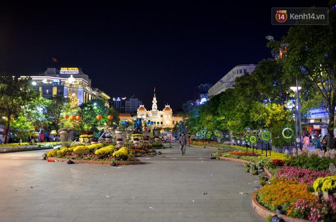 Từ khoảng 21h tối mùng 4 Tết, sau lễ bế mạc đường hoa Nguyễn Huệ được công nhân tiến hành dọn dẹp. Ảnh: Abu Nguyễn