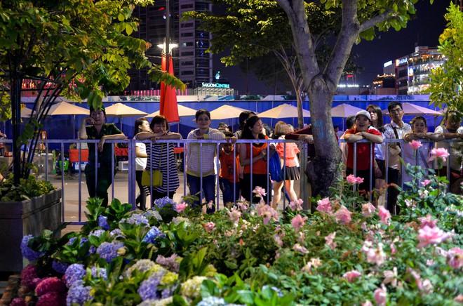 Một số người dân đừng chờ sẵn phía bên ngoài hàng rào để xin những chậu hoa tươi