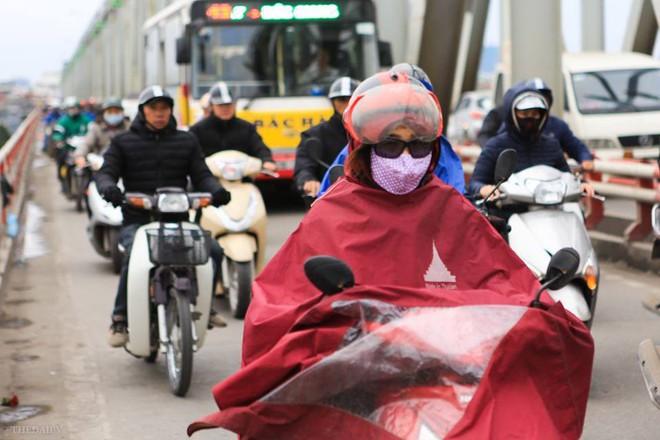 Chùm ảnh: Người dân Hà Nội khoác cả chăn bông, mặc áo mưa xuống phố để tránh rét - Ảnh 5.