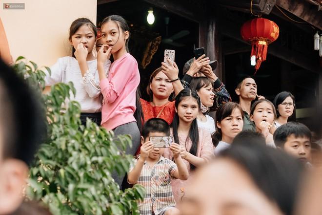 Hàng trăm người dân tập trung đông đúc chứng kiến nghi thức ché.m lợn. Tiếng lợn kêu lớn khiến một số người nhăn nhó.