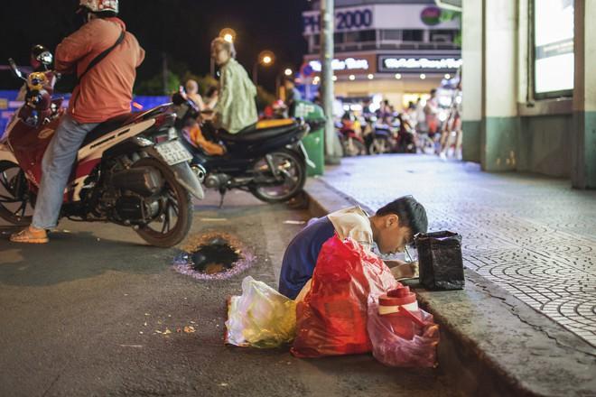 Hình ảnh người mẹ nghèo uốn nắn cho con từng nét chữ trên vỉa hè bên hông chợ Bến Thành gây xúc động mạnh - Ảnh 2.