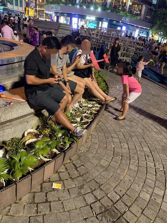 Bức xúc hình ảnh hàng chục người ngồi bên đài phun nước phố đi bộ Hồ Gươm, thản nhiên đạp chân thẳng lên hàng hoa trang trí - Ảnh 1.