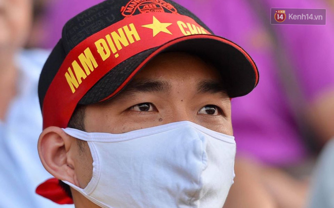 CĐV Nam Định được đo thân nhiệt và yêu cầu đeo khẩu trang vào sân trong trận đấu chuyên nghiệp đầu tiên trên thế giới có khán giả sau Covid-19 - ảnh 13