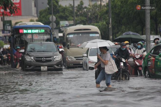 Đường phố Sài Gòn ngập lênh láng sau cơn mưa lớn, người dân khổ khổ dắt xe lội nước trên đường - ảnh 14