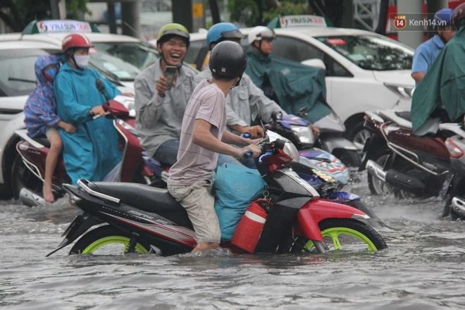 Đường phố Sài Gòn ngập lênh láng sau cơn mưa lớn, người dân khổ khổ dắt xe lội nước trên đường - ảnh 11