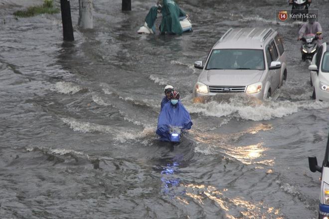Đường phố Sài Gòn ngập lênh láng sau cơn mưa lớn, người dân khổ khổ dắt xe lội nước trên đường - ảnh 7