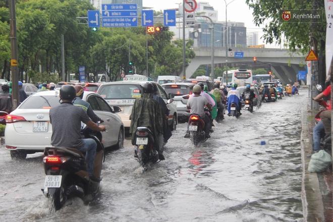 Đường phố Sài Gòn ngập lênh láng sau cơn mưa lớn, người dân khổ khổ dắt xe lội nước trên đường - ảnh 19