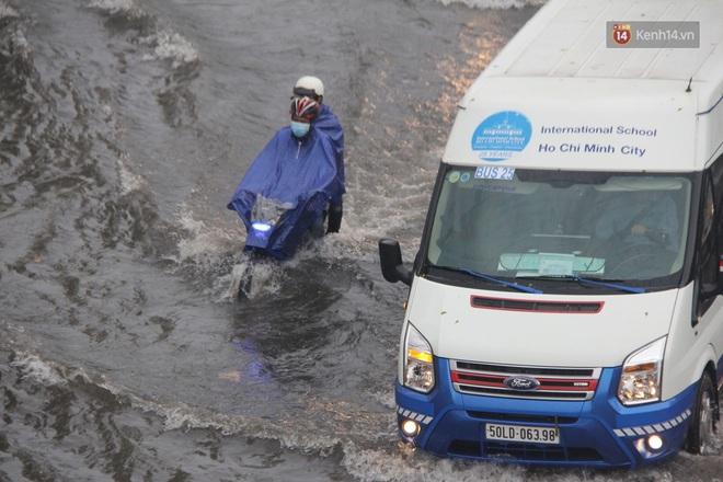 Đường phố Sài Gòn ngập lênh láng sau cơn mưa lớn, người dân khổ khổ dắt xe lội nước trên đường - ảnh 16