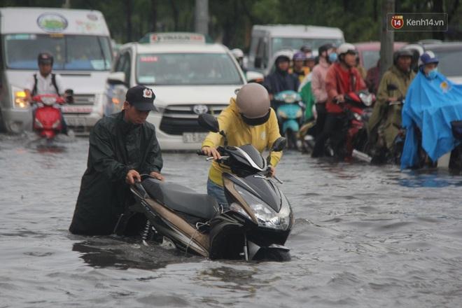 Đường phố Sài Gòn ngập lênh láng sau cơn mưa lớn, người dân khổ khổ dắt xe lội nước trên đường - ảnh 9