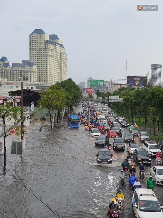 Đường phố Sài Gòn ngập lênh láng sau cơn mưa lớn, người dân khổ khổ dắt xe lội nước trên đường - ảnh 1