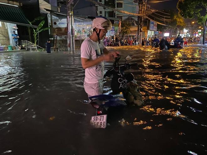 Nhiều tuyến đường Sài Gòn ngập lút bánh xe sau mưa lớn, nước chảy cuồn cuộn như lũ - Ảnh 5.
