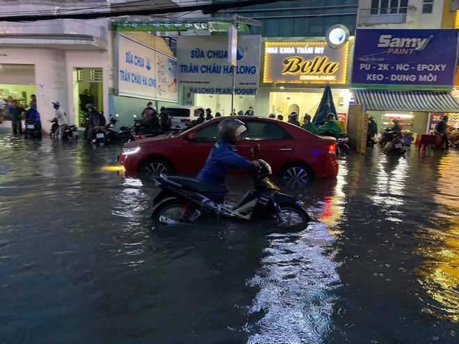 Nhiều tuyến đường Sài Gòn ngập lút bánh xe sau mưa lớn, nước chảy cuồn cuộn như lũ - Ảnh 14.