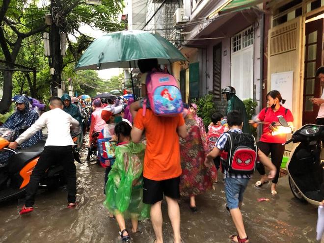 Ảnh: Cơn mưa xối xả đổ xuống Hà Nội giờ tan học khiến nhiều phụ huynh, học sinh mệt nhoài trên đường về nhà - ảnh 2