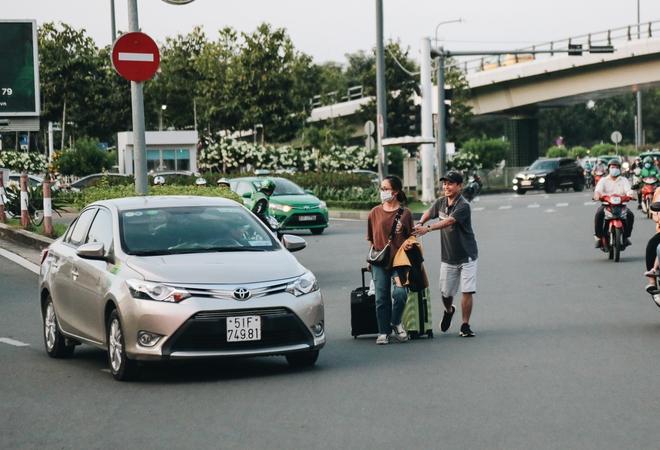 Khổ như hành khách ở Tân Sơn Nhất: Dang nắng mang vác hành lý ra đường đón xe công nghệ - Ảnh 12.
