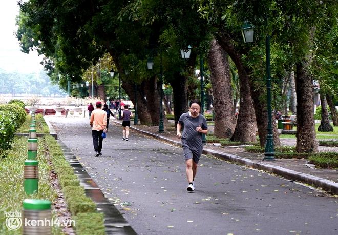 Ảnh: Buổi sáng đầu tiên công viên Hà Nội mở cửa trở lại, người dân phấn khởi đội mưa đi dạo, khiêu vũ - ảnh 1