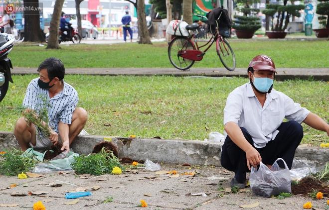 ẢNH: Sau khi tiểu thương ở Sài Gòn vứt bỏ hoa ế, nhiều người dân tranh thủ đến xin đất, lượm hoa mang về trưa 30 Tết - Ảnh 4.