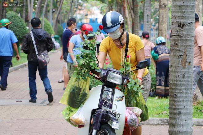 ẢNH: Sau khi tiểu thương ở Sài Gòn vứt bỏ hoa ế, nhiều người dân tranh thủ đến xin đất, lượm hoa mang về trưa 30 Tết - Ảnh 2.