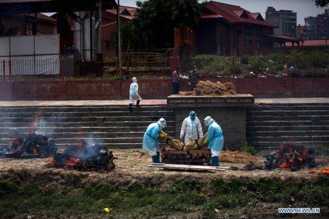Địa ngục Covid thứ 2: Lò hỏa táng quá tải, quốc gia hàng xóm của Ấn Độ cũng buộc phải hỏa thiêu thi thể ngoài trời - ảnh 1