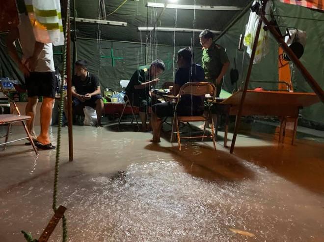 Xót xa hình ảnh chiến sĩ công an dầm mưa tại chốt phòng dịch Covid-19: Những bữa cơm ăn vội, mưa xối trên đầu và nước ngập dưới chân - Ảnh 1.